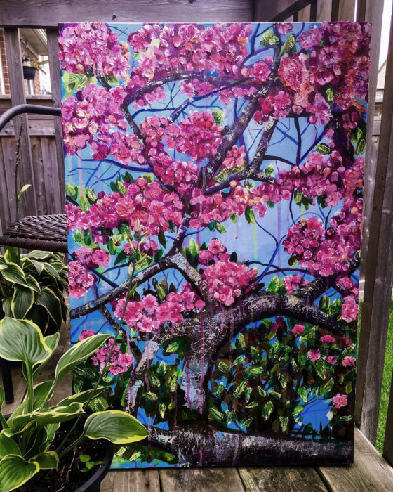An acrylic painting of cherry blossoms sitting outside with potted plants